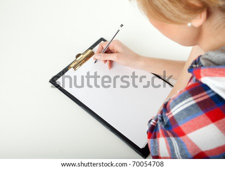 young woman writing on black clipboard