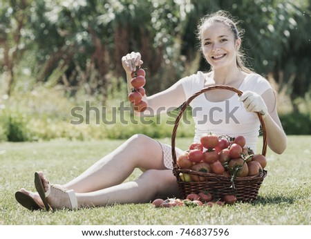 Young woman 20-25 years old with basket of harvested tomato in garden