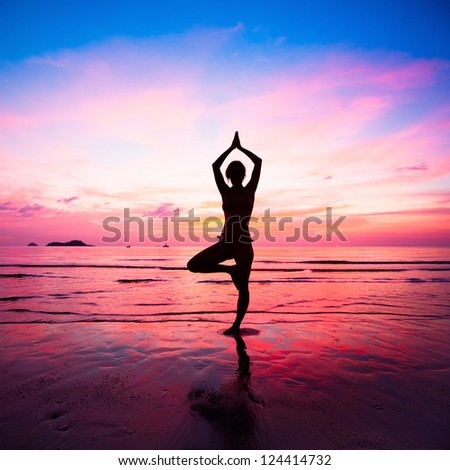 Young woman yoga practice at the seaside at sunset