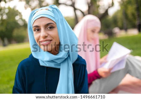 Young woman. Young woman wearing bright blue hijab holding orange tablet smiling broadly #1496661710
