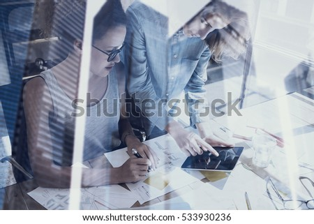 Young womans working in modern design studio.Two girls using electronic tablet on workplace.Double exposure,skyscraper office building blurred background.Horizontal stock photo