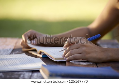 Young women and education, close up of hands of girl studying for college exam in park. Side view, copy space