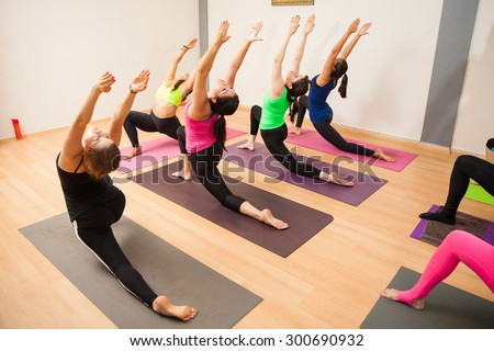 Young women and instructor working out together in their yoga class at a gym