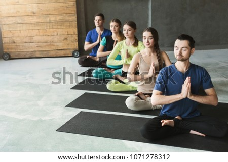 Young women and men in yoga class, meditation exercises. Lotus pose for relaxation. Healthy lifestyle in fitness club, crop, copy space #1071278312