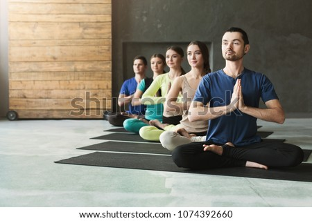Young women and men in yoga class, meditation exercises. Lotus pose for relaxation. Healthy lifestyle in fitness club, crop, copy space, selective focus