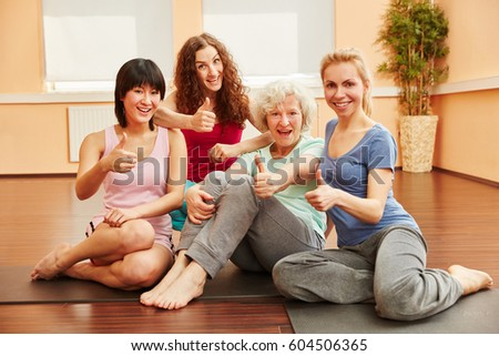 Young women and senior woman holding thumbs up after yoga class