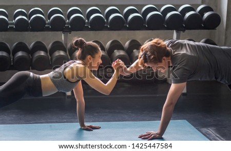 Young women and young men touch hands to exercise in the gym.