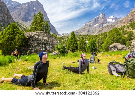 Young women doing morning fitness in mountain landscape.\ Two female athletes on green grass lawn doing yoga sport exercises outdoor day sunlight blue sky and mountains on background