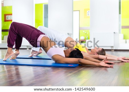 Young women doing yoga and meditation in gym for better fitness, caucasian and latina people