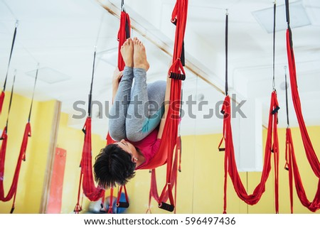 Young women doing yoga exercise or aerial yoga antigravity light in the studio. #596497436