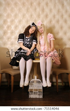 Young women dressed as dolls, sleep sitting on the table in the doll house.