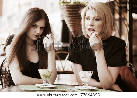 Young women eating an ice cream at sidewalk cafe