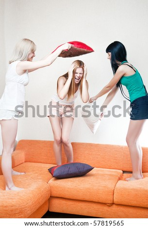 Young women fighting on pillows. Bright white colors.