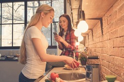 Young women friends cooking meal together at home