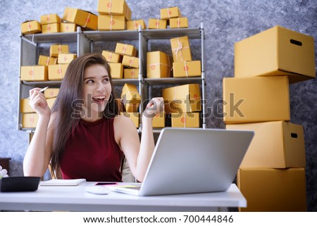 Young Women happy after new order from customer, business owner working at home office packaging on background. online shopping SME entrepreneur or freelance working concept.