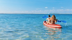 Young women have fun on boat walk. Girls paddling on kayak by sea lagoon. Travel lifestyle, recreational activity, watersports on summer beach family vacation.