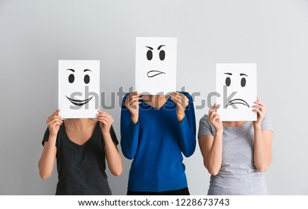 Young women hiding faces behind sheets of paper with drawn emoticons on light background #1228673743
