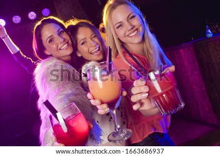 Young women holding cocktail in nightclub, portrait