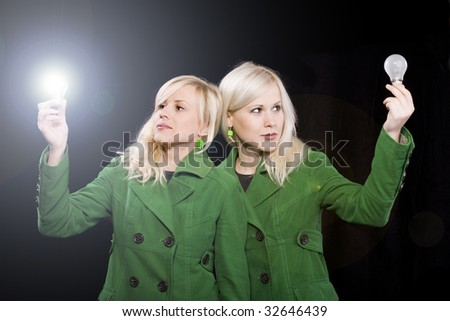 Young women holding working light bulb and other is off. Beautiful sister with idea concept