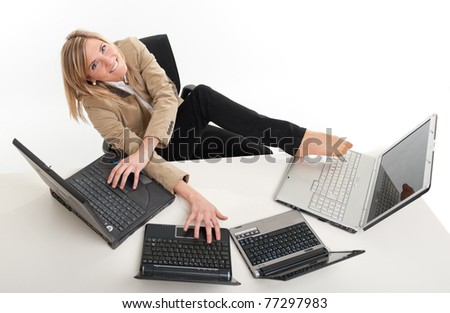 Young women in a desk overcrowded with computers typing with both hands and feet