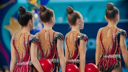 Young women in colorful bright costumes walking out from the stage of the rhythmic gymnastics tournament