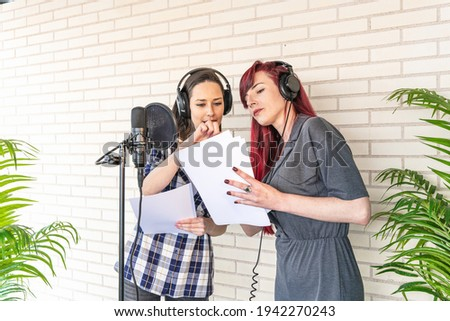 Young women in headphones discussing script while standing near microphone against brick wall in film dubbing studio Stok fotoğraf ©