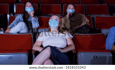 Young women in masks watch movie at cinema. Media. Watching movies in cinemas in context of coronavirus pandemic. People sit in protective masks sitting in movie theater