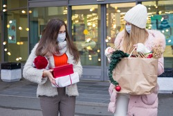 Young women in medical mask shopping for Christmas in mall. Xmas holidays in new Covid-19 reality.