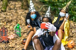 Young women in witch halloween costumes on coronavirus year. Girls making selfies. Focus on smartphone. Halloween and virus concept.
