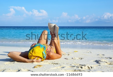 Young women is reading on coral beach, Maldives