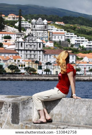 Young women is sitting at the pier of the Marina in Horta  Faial Island, Azores