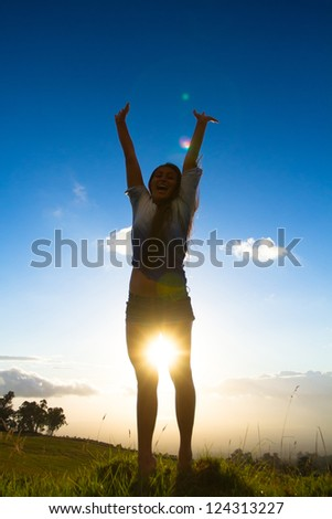 Young women joyfully jumping with sunset in background