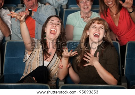 Young women laugh out loud in theater