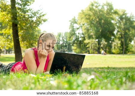 Young women lying on grass in park and using laptop