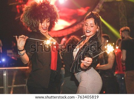Young women making party with fireworks inside night club - Trendy fashion girls having fun at dance festival - Youth and enjoying nightlife concept - Focus right person face
