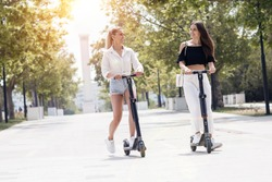 young women on electro scooter in city park. Two girls riding scooter in sunset light in street