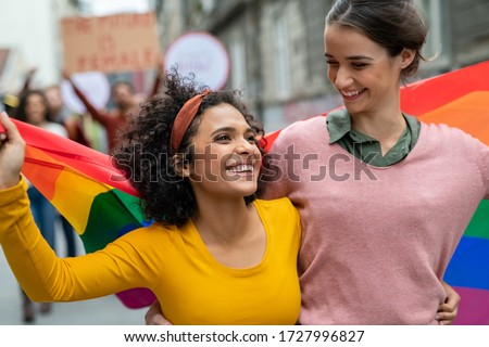 Young women on street enjoying holding gay pride flag during protest. Smiling multiethnic women enjoying during march on street for lgbt rights. Diversity, tolerance and gender identity concept.