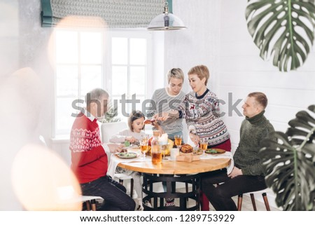 young women putting meat on the guests' plates. appetizing turkey for the whole family #1289753929