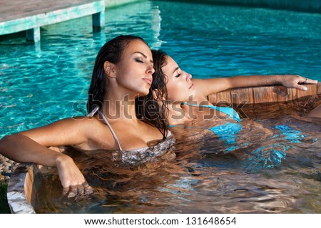 young women relaxing in outdoor jacuzzi by the pool summer day