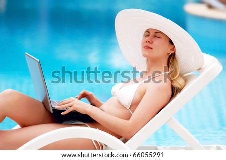 Young women relaxing near waterpool with laptop.