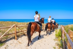 Young women riding horses to sandy beach in Lubiatowo coastal village, Baltic Sea, Poland