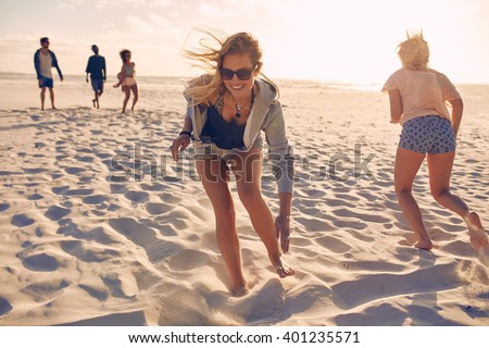 Young women running race on the beach. Group of young people playing games on sandy beach on a summer day. Having fun on the beach.