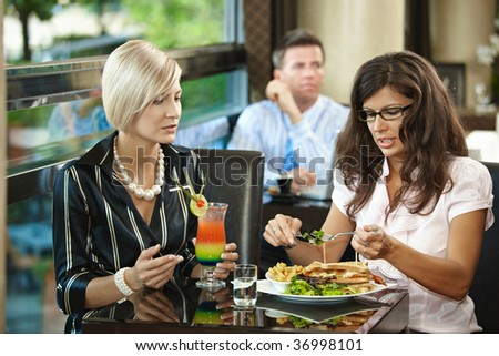 Young women sitting at table, eating sandwich and drinking cocktail in restaurant.