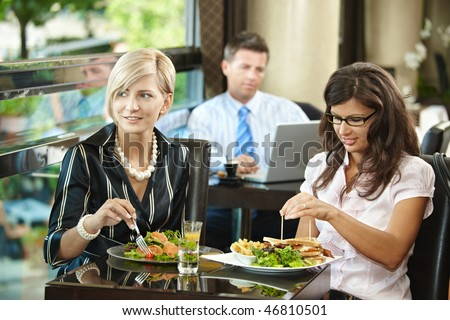 Young women sitting at table, eating sandwich and salad in restaurant, smiling.