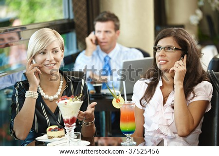 Young women sitting in cafe having sweets, talking on mobile phone.