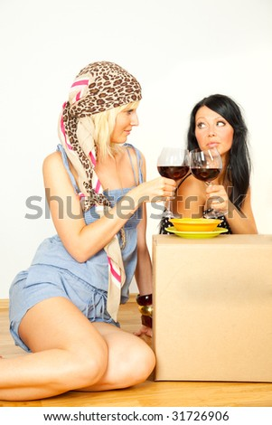 Young women sitting on floor and drinking wine and celebrating the new real estate apartment on move carton