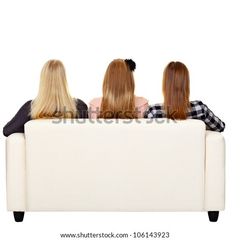 Young women sitting on sofa - rear view. Isolated on white