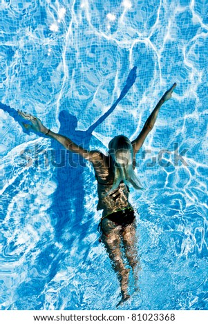 Young women swimming under blue  water in swimming pool - stock photo
