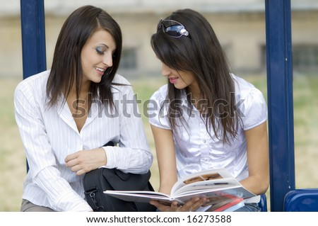 young women talking together about a make up book at the bus stop in the central town