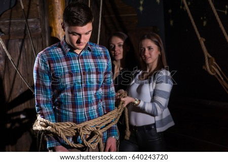 Young women tie a young sad guy to a column on the deck of a ship, escape the room game concept #640243720